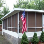 custom screen room built onto a mobile home with large American flag
