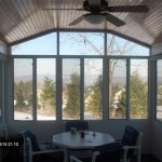 sunroom with wooden ceiling and fan and great view of woods