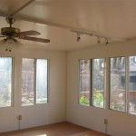 sun room with ceiling fan and custom lighting fixtures installed