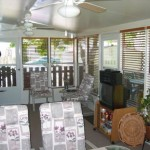 custom sun room with TV, furniture, ceiling fan and space heater