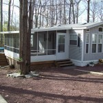 large screen room attached to mobile home in the woods