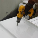 contractor using drill to attach new roof to mobile home