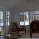 wicker furniture placed in sun room with view of Winter weather
