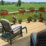 custom deck installed with patio furniture and potted plants