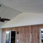 large ceiling fan installed inside custom home addition with sliding doors