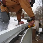 contractor at work installing new roof for mobile home
