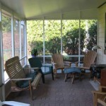 sun room with stone patio floor and lawn furniture inside