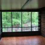 view of the woods from inside sunroom of log house
