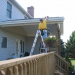 contractor adding finishing touches to back porch awning
