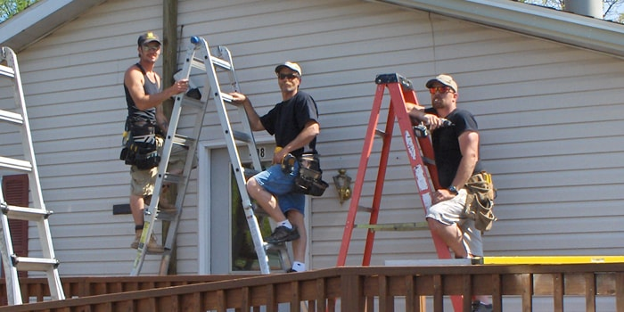contractor crew replacing siding on ladders